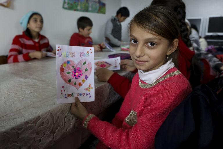 Una chica en Romania mostrando una carta